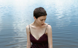 Girl with short hair on the background of water looking away Royalty Free Stock Image