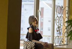 A girl with short hair in a black dress sits next to a window stock photo