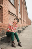 Girl with short hair. Outdoor portrait of young woman wearing checkered shirt and jeans royalty free stock photo