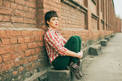 Girl with short hair. Outdoor portrait of young woman wearing checkered shirt and jeans stock photography
