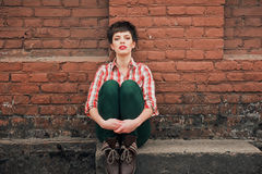 Girl with short hair. Outdoor portrait of young woman wearing checkered shirt and jeans royalty free stock photos