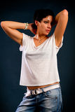 Girl with short hair. Wearing a white t-shirt and jeans against a dark background Stock Photo