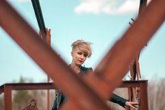 Girl with a short haircut on the bridge against the sky royalty free stock photos