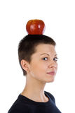 Girl with a short hairstyle and apple on a head Stock Photography