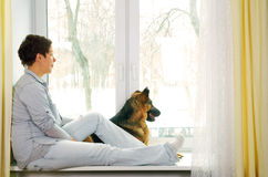The girl with a short hairstyle in jeans clothes waits. For someone sitting on a window sill and stroking a dog Stock Images