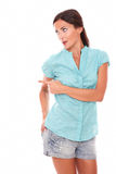 Girl in short jeans looking at her right pointing Stock Photography
