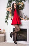 Girl in a short red dress in front of fireplace Royalty Free Stock Photography