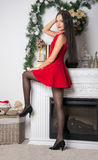 Girl in a short red dress in front of fireplace Royalty Free Stock Photos