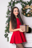 Girl in a short red dress with a gift in hand on background fire Stock Photo