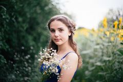 A girl in short shorts and a blue T-shirt with a bouquet of wild flowers royalty free stock photos