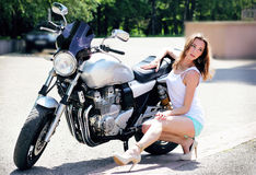 Girl in short shorts posing near a motorcycle Royalty Free Stock Images