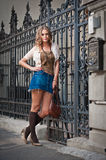 Girl short skirt and bag walking on street.Young European Girl in Urban Setting. Sexy woman dressed provocatively and posing on street.Blonde attractive woman Stock Photos