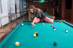 Girl in short skirt playing snooker Stock Images