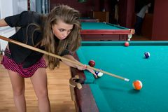 Girl in short skirt playing snooker Stock Photos