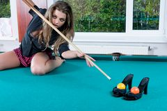 Girl in short skirt playing snooker Royalty Free Stock Images