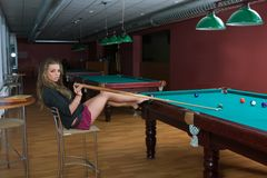 Girl in short skirt playing snooker Royalty Free Stock Photos