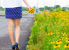 Girl with short skirt walks in the flower garden Stock Photo