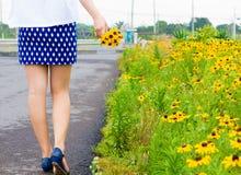 Girl with short skirt walks in the flower garden Stock Photo