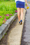 Girl with short skirt walks in the flower garden Royalty Free Stock Images