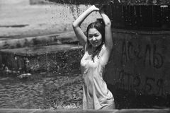 Girl in a short slinky wet dress with long wet hair in water droplets in the city fountain Stock Photography