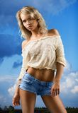 Girl in shorts on a background of the sky. Royalty Free Stock Image
