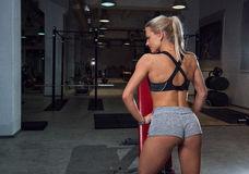 Girl in shorts. Beautiful sexy girl in short shorts is standing with her back in the gym Stock Image