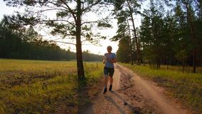 Girl in shorts and blue glasses running on a country road at sunset. Slow motion stock video footage