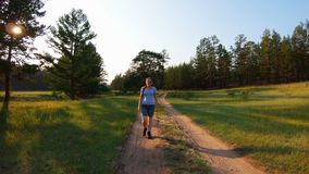 Girl in shorts and blue glasses walking on a country road at sunset. Front view stock footage
