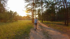 Girl in shorts and blue glasses walking on a country road at sunset. Slow motion, bright sunlight stock video