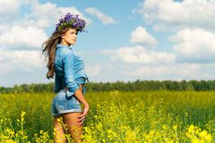 Girl in shorts and chaplet in a field. Beautiful young brunette in shorts and chaplet in a yellow field Stock Image
