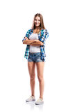 Girl in shorts and checked shirt, arms crossed, isolated. Standing teenage girl in denim shorts , tight singlet, blue checked shirt and canvas sneakers, arms Royalty Free Stock Photos