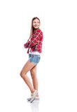 Girl in shorts and checked shirt, arms crossed, isolated. Standing teenage girl in denim shorts , tight singlet, red checked shirt and canvas sneakers, arms Royalty Free Stock Photo