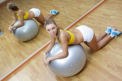 Girl in shorts do exercise on big ball in gym Royalty Free Stock Image