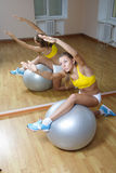 Girl in shorts do exercise on big ball in gym Royalty Free Stock Photos