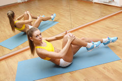 Girl in shorts do exercise on floor mat in fitn Stock Photography