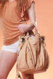 Girl in shorts holding beige bag orange background Royalty Free Stock Image