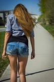 Girl in shorts riding a skateboard Stock Photo