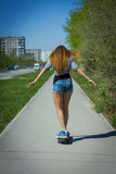 Girl in shorts riding a skateboard Royalty Free Stock Photo