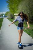 Girl in shorts riding a skateboard Royalty Free Stock Image