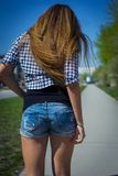 Girl in shorts riding a skateboard Stock Photography