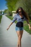 Girl in shorts riding a skateboard Royalty Free Stock Photos