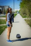 Girl in shorts riding a skateboard Royalty Free Stock Photography