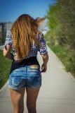 Girl in shorts riding a skateboard Stock Photos
