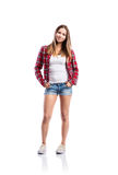 Girl in shorts and shirt, hand in pockets, isolated. Standing teenage girl in denim shorts, tight singlet, red checked shirt and sneakers, hands in the pockets Royalty Free Stock Photo