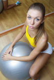 Girl in shorts sitting with big ball in gym Royalty Free Stock Image