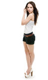 The girl in shorts standing. On a white background Stock Images