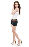 The girl in shorts standing. On a white background Stock Image