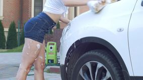 Girl in shorts to wash car stock video footage