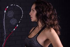 Young athletic girl with a squash racket on a dark background. stock photo