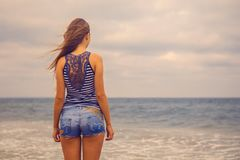 Girl in shorts walking on the beach royalty free stock photography